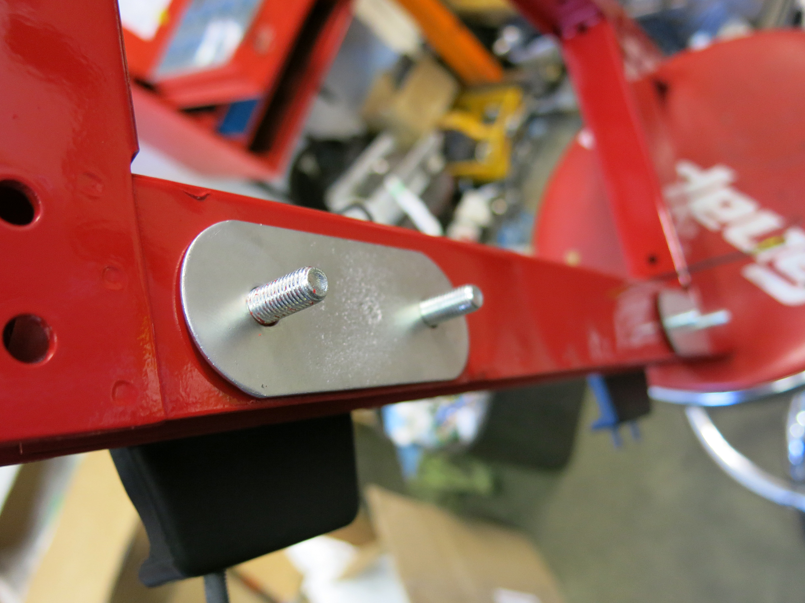 STEP 5 - Install the E-Type front cross member aka the 'Picture Frame' with the lower 4  5/16x2¼bolts.  These sheet metal spacers sit between the picture frame and engine subframes. If your car is a 4.2 the horn brackets will also go through these four bolts.
