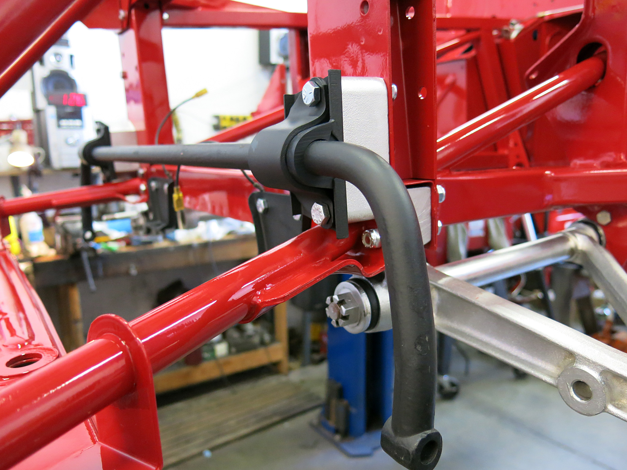 STEP 12 - Loosely attach the sway bar. Only two bolts hold on the sway bar but they pass through more layers than anything else on the car. Usually a second person is helpful here not to scratch the paint and keep all the pieces intact before the long bolts can be threaded through.