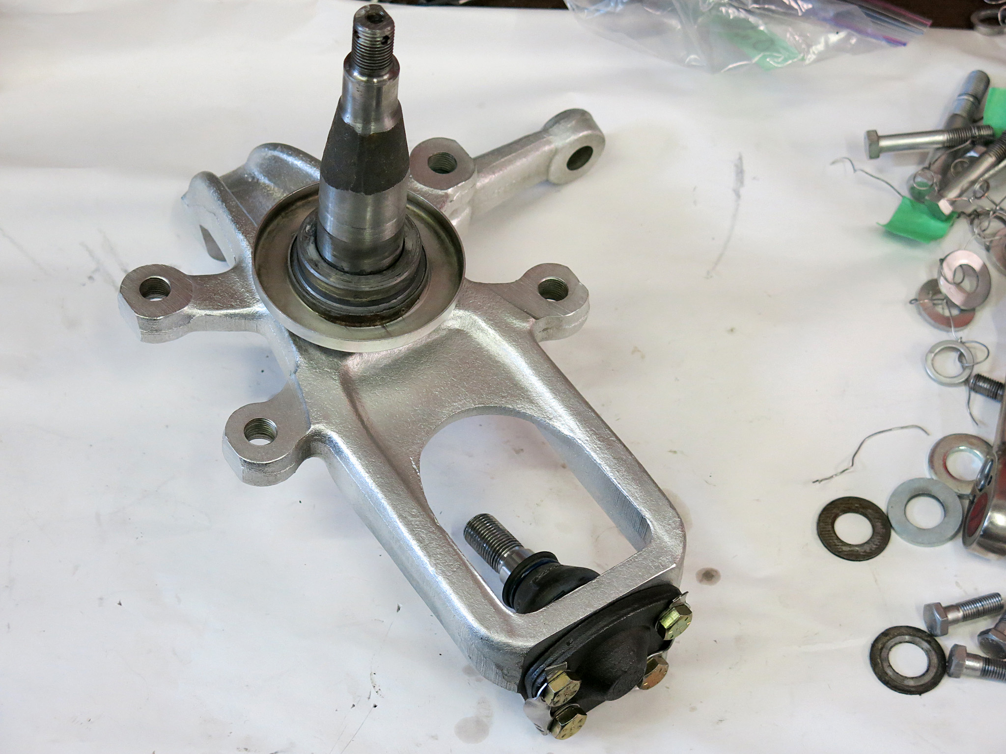 STEP 17 - Prepare the front spindle by attaching the lower ball joint. Ours has an XJ40 unit which is sealed and need smaller bolts 5/16-3/4 bolts. We still used the paired tab washers.